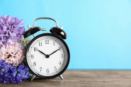 Black alarm clock and spring flowers on light blue background, space for text. Time change