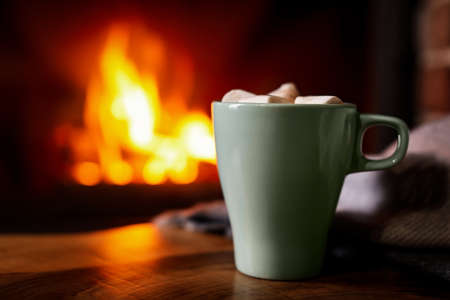 Delicious sweet cocoa with marshmallows and blurred fireplace on background Standard-Bild