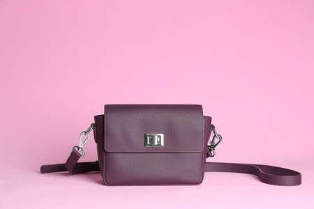 Stylish woman's bag on light pink background