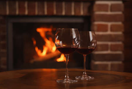 Glasses of red wine on wooden table near fireplace. Space for text