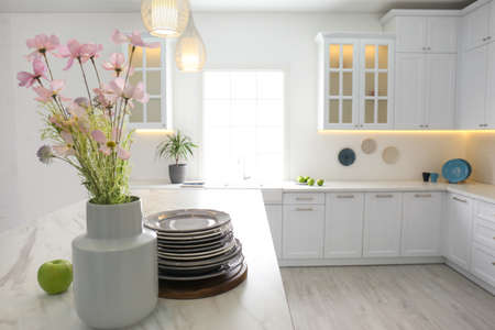 Beautiful flowers and dishware on white marble table in modern kitchen Banque d'images