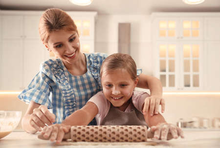Mother and daughter rolling dough together in kitchen