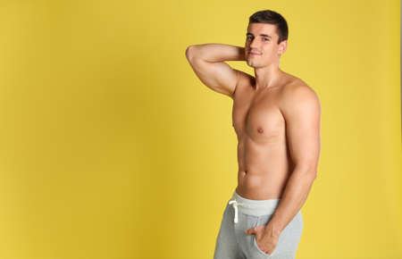 Man with sexy body on yellow background. Space for text