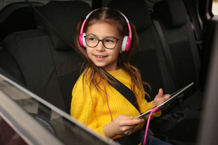 Cute little girl listening to audiobook in car