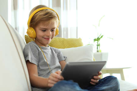 Cute little boy with headphones and tablet listening to audiobook at home