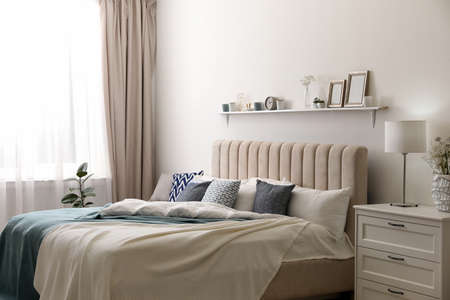 Comfortable bed with pillows in room. Stylish interior design