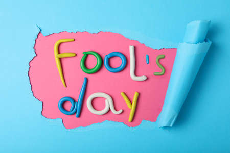 Flat lay composition with words FOOL'S DAY made of clay on color background. April holiday