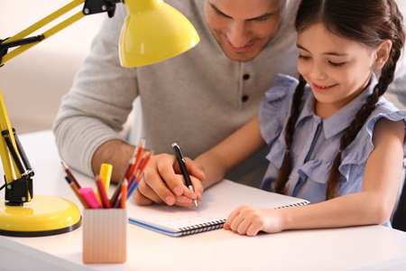 Man helping his daughter with homework at table indoors Banque d'images