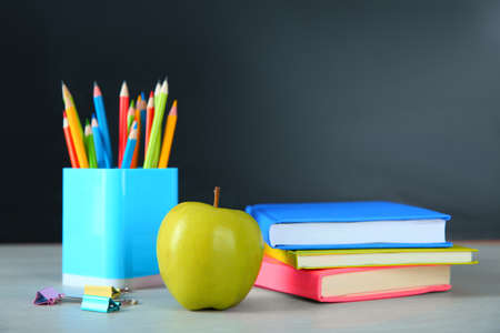 Apple and school stationery on white wooden table. Doing homework