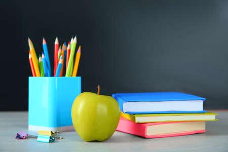 Apple- und Schulbriefpapier auf weißem Holztisch. Hausaufgaben machen