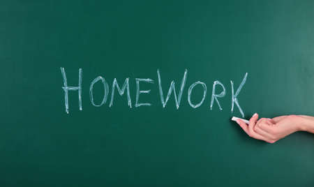 Woman writing word HOMEWORK on chalkboard, closeup