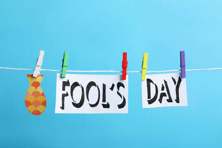 Words FOOL'S DAY and paper fish with pegs on laundry line against light blue background. April holiday