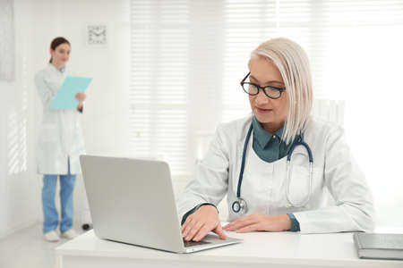 Mature female doctor working with laptop at table in office