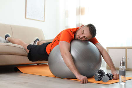 Lazy young man with sport equipment at home 版權商用圖片