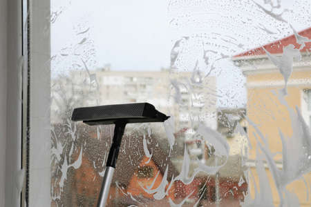 Cleaning window with squeegee indoors. Space for text