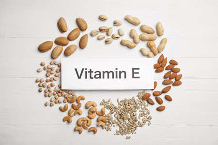 Card with phrase Vitamin E and different products on white wooden table, flat lay