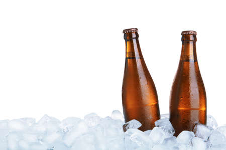 Ice cubes and bottles of beer on white background