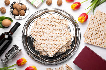 Flat lay composition with symbolic Pesach (Passover Seder) items on white wooden table Foto de archivo