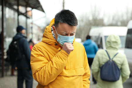 Asian man wearing medical mask on city street. Virus outbreak