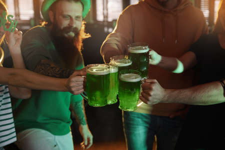 Group of friends toasting with green beer in pub, closeup. St. Patrick's Day celebration