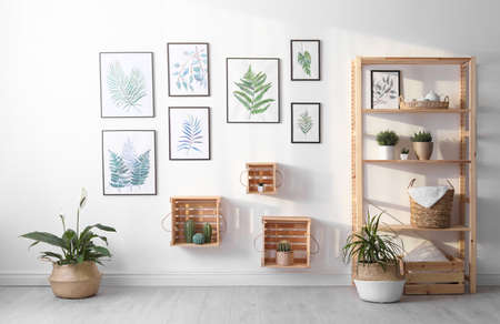 Beautiful paintings of tropical leaves on white wall in living room interior Standard-Bild