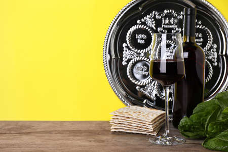 Symbolic Pesach (Passover Seder) items on wooden table against yellow background, space for text Imagens