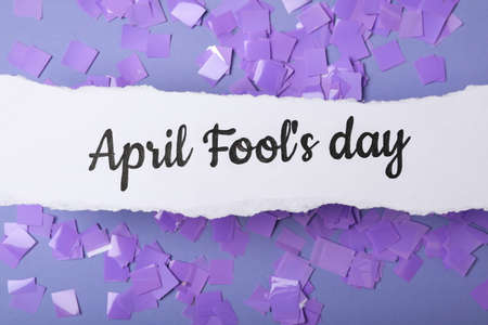 Paper note with phrase APRIL FOOL'S DAY and confetti on lilac background, flat lay