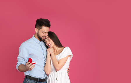 Man with engagement ring making marriage proposal to girlfriend on crimson background