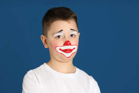 Preteen boy with clown makeup on blue background, space for text. April fool's day