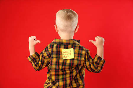 Little boy with APRIL FOOL'S DAY sticker on back against red background Banco de Imagens