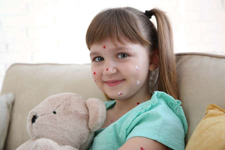 Little girl with chickenpox sitting on sofa at home