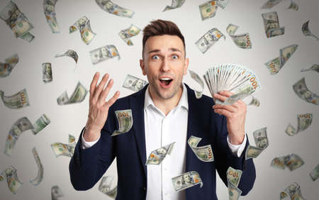 Happy young man with dollars under money rain on light background Фото со стока