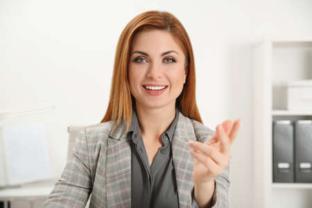 Happy woman using video chat in modern office, view from web camera Foto de archivo