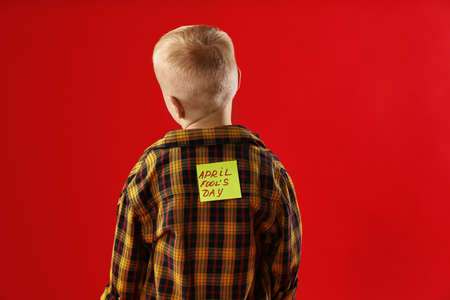 Little boy with APRIL FOOL'S DAY sticker on back against red background 免版税图像