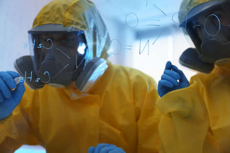 Scientists in chemical protective suits writing formula on glass board at laboratory. Virus research