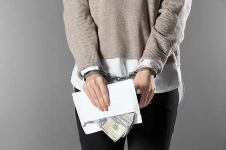 Woman in handcuffs holding bribe money on grey background, closeup