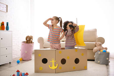 Cute little children playing with cardboard ship and binoculars at home