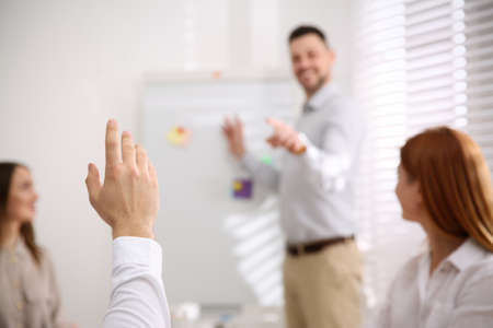 Young man raising hand to ask question at business training in conference room, closeup Stock Photo