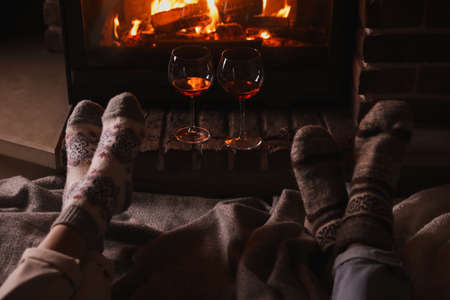 Couple and glasses of red wine near burning fireplace, closeup Imagens