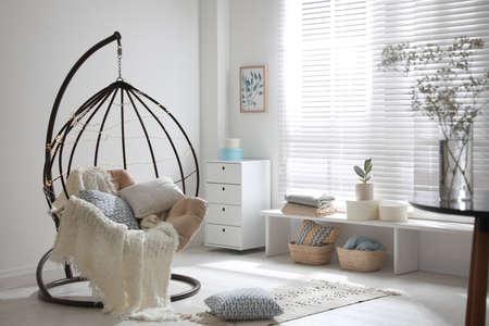 Fauteuil suspendu confortable avec guirlandes lumineuses dans un salon moderne. Design d'intérieur