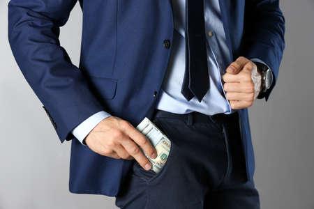 Man putting bribe into pocket on grey background, closeup