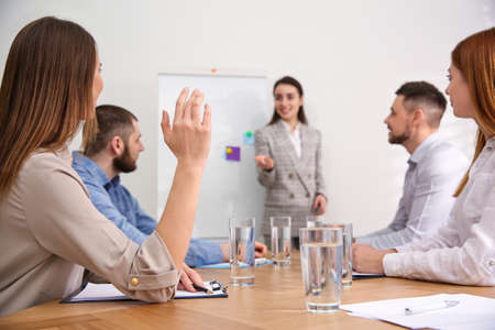 Young woman raising hand to ask question at business training in conference room Stock Photo