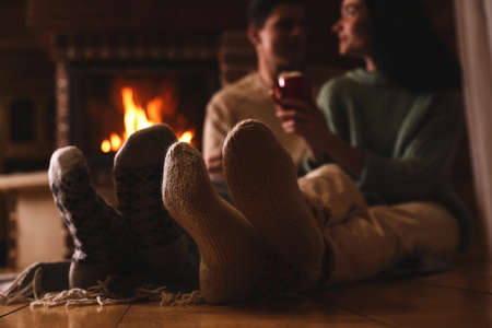 Lovely couple with delicious cocoa near fireplace at home, focus on feet. Winter vacation