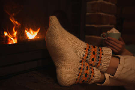 Woman in knitted socks with cup of sweet cocoa near fireplace indoors, closeup
