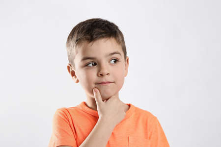 Emotional little boy in casual outfit on white background
