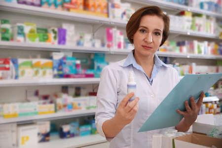 Pharmacien professionnel avec presse-papiers et médicaments en pharmacie Banque d'images
