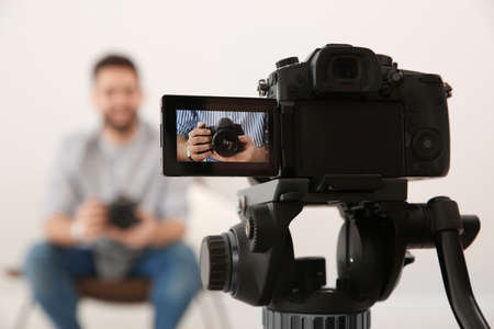 Young blogger with camera recording video indoors, focus on screen
