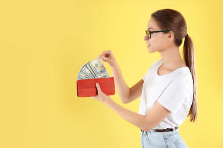 Young woman with wallet full of money on yellow background 写真素材