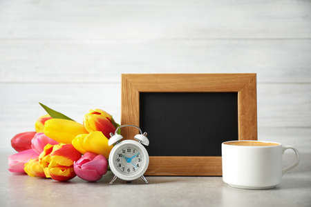 Chalkboard with morning wish, delicious coffee, tulips and alarm clock on light grey table Reklamní fotografie