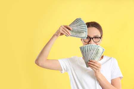 Young woman with money on yellow background